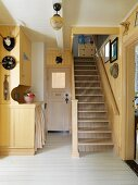 Wood-clad foyer painted pale yellow with staircase in old country house