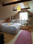 Attic bedroom; double bed with white bedspread in front of raised platform with white wooden balustrade