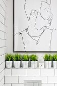 Modern line drawing portrait on tiled wall in bathroom above row of decorative grasses in zinc pots on masonry shelf