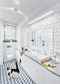 Cat in white, modern bathroom with tiled walls & floor, long washstand with base cabinets & strip light over mirror; modern artwork above wall-mounted toilet in background