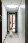 Family in narrow corridor with skylight and white fitted cupboards
