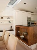 Upholstered dining chairs in front of solid wood kitchen counter an white fitted cupboards in open-plan kitchen