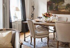 Gepolsterte beigefarbene Stühle an rustikalem Esstisch in Wohnzimmerecke mit traditionellem Flair