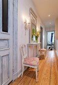 Schmaler, langer Flur mit rustikalem Dielenboden; zwei antike, neu gepolsterte Stühle umrahmen weißen filigranen Wandtisch mit Spiegel