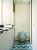 Spherical laundry basket with lid on patterned tiled floor of utility room