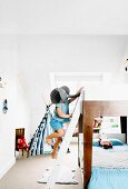 Child wearing elephant mask climbing loft-bed ladder