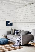 Modern grey sofa with row of scatter cushions, sisal rug on wooden floor in corner of room with white wooden cladding
