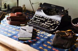 Vintage typewriter, sunglasses and notebook on wooden table with folklore blanket
