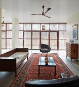 Seating area with retro leather armchairs, purist wooden sofa and Oriental rug with subdued light falling through glass wall with sun screens
