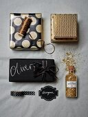 Christmas gifts wrapped in black and gold paper with matching ribbons arranged with gold glitter