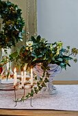 Festive arrangement of hellebores in glass goblet dish and wreath-shaped candelabra on dresser
