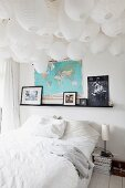 Double bed with white bed linen below a sea of paper lanterns on ceiling