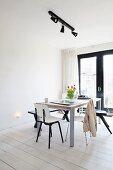 Dining area below black spotlights on lighting rail in minimalist interior with white-painted wooden floor