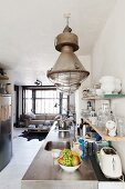 Kitchen counter with stainless steel worksurface below industrial-style pendant lamps in open-plan interior
