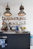 Vintage, industrial-style pendant lamps above modern kitchen counter with stainless steel worksurface and black doors; minimalist shelves of crockery on wall