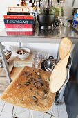 Retro bar stool with wooden seat and backrest next to kitchen utensils on shelves with castors