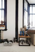 Exercise equipment on floor and side table with wooden top on black metal frame