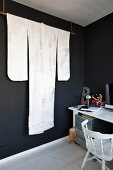 Elegant white kimono displayed on rod suspended from ceiling in black-painted room next to desk