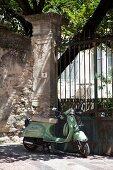 Retro Vespa vor hohem Gartentor aus Metall