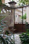 Blick auf Eingangstor aus Metall, seitlich antike Bank vor Gartenmauer