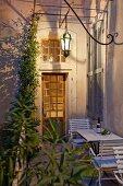 Laternenbeleuchtung über Tische und Stühle vor Hauswand mit geschlossenen Fensterläden