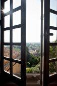 Halb geöffnete Sprossenfenster mit Ausblick auf mediterrane Landschaft