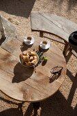 Blick auf runden Holztisch und Sitzbank auf gekiester Terrasse