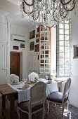 Rokoko Stühle an gedecktem Tisch, vor offenem Fenster, Kronleuchter mit Glasschmuck