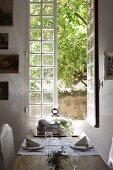 Gedeckter Tisch vor offenem Fenster mit Blick in Innenhof