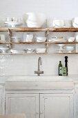 Küchenzeile mit rustikalem Spülbecken in Unterschrank, oberhalb weisses Geschirr auf rostiger Ablage