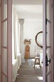 Blick durch offene Flügeltür auf Säule und Holzstele mit antiker Schale