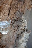 Wasserglas auf verwittertem Baumstamm
