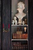 Ausschnitt eines Schrankes, hinter Glastür verschiedene Büsten und antiquarische Bücher