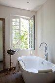Freistehende Badewanne mit Standarmatur vor offenem Fenster