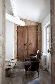Blick durch offene Tür auf antike Sessel im Rokoko Stil, im Hintergrund rustikale Holztür