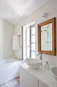 Waschtisch mit Waschschüsseln auf weißem Unterschrank, an Wand Spiegel mit hellem Holzrahmen, in ländlichem Bad