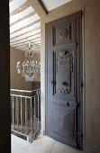 Geschnitzte Tür neben Treppengeländer, im Hintergrund traditioneller Kronleuchter