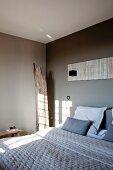 Schlafzimmer mit grau getönten Wänden, auf Doppelbett gestepptes Plaid