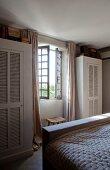 Schränke mit Lamellentür neben Sprossenfenster im Schlafzimmer