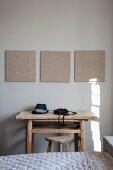 Blick über Bett auf rustikalen Tisch und Hocker aus Holz
