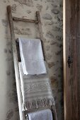 Alte Holzleiter als Handtuchhalter an Natursteinwand lehnend