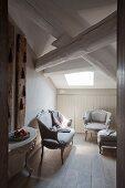 Blick in ländliches Dachzimmer auf Rokoko Sitzbank und Sessel mit Fussschemel