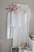 White vintage clothing hung on white wooden panel on pastel wall