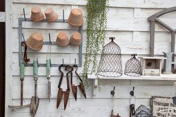 Garden tools and plant pots hung on white-painted wooden panel