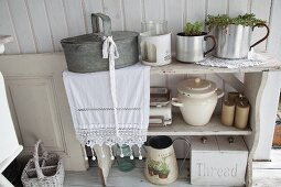 Kitchen utensils on vintage shelves and zinc container on lace runner