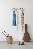 Curved vintage spoons inserted through suspended wooden rod used as coat rack above old guitar case and hockey sticks in basket