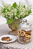 Biscuits in glass jar and on plate in front of vase of lily-of-the-valley on brown tablecloth with white polka dots