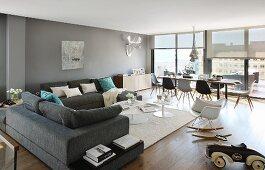 Überecksofa und Essplatz mit Klassikerstühlen von Eames in weitläufigem Penthouse-Wohnraum