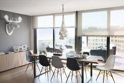 Essplatz mit Eames Chairs vor Fensterfront in Penthouse-Wohnung; Deko-Geweih an der Wand