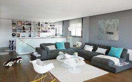 Moderner, grau-weiss gestalteter Wohnraum mit großzügiger Sofalandschaft; im Hintergrund Maisonette-Treppe und Einbauregal